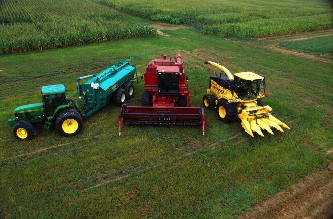 Un tracteur, une moissonneuse et une ensileuse dans un champ